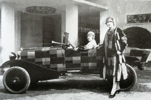 Two models wearing fur coats with a car painted after Sonia Delaunay's fabrics, 1925